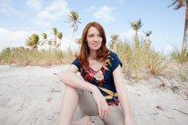 Portrait de jeune femme assise sur la plage — Photo de stock