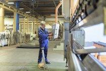 Engineer operating steel bending machine in engineering factory — Stock Photo