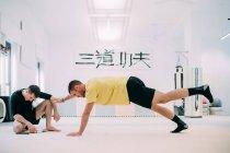 Man with coach doing push ups — Stock Photo