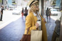 Woman with coffee to go window shopping, Cape Town, South Africa — Stock Photo