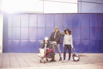 Vue éloignée de fille avec les parents sur le chariot de bagages d'équitation — Photo de stock