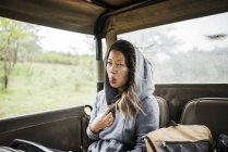 Junge Touristin zeigt Zunge im Tourtruck, Kruger Nationalpark, Südafrika — Stockfoto