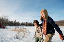 Fratello e sorella che camminano sulla terra innevata — Foto stock