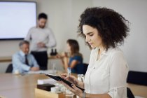 Бізнес-леді в офісі, використовуючи цифровий планшетний Зустрічаючись — стокове фото