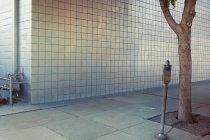 Міських тротуарі з дерева і паркування автомата уздовж сірих стін — стокове фото