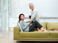 Mature couple sitting on sofa with wine — Stock Photo