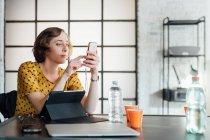 Бізнес-леді за допомогою смартфона в офісі таблиці — стокове фото