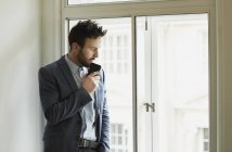 Businessman holding smartphone and looking out of window — Stock Photo