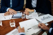 Businessmen and woman at boardroom table using digital tablet and working on paperwork, cropped — Stock Photo