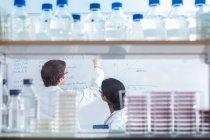 Científicos en ambiente de aislamiento usando máscaras, trabajando en laboratorio de investigación. - foto de stock
