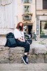 Молодая женщина в маске во время Короны, сидит на улице, смотрит в камеру. — стоковое фото