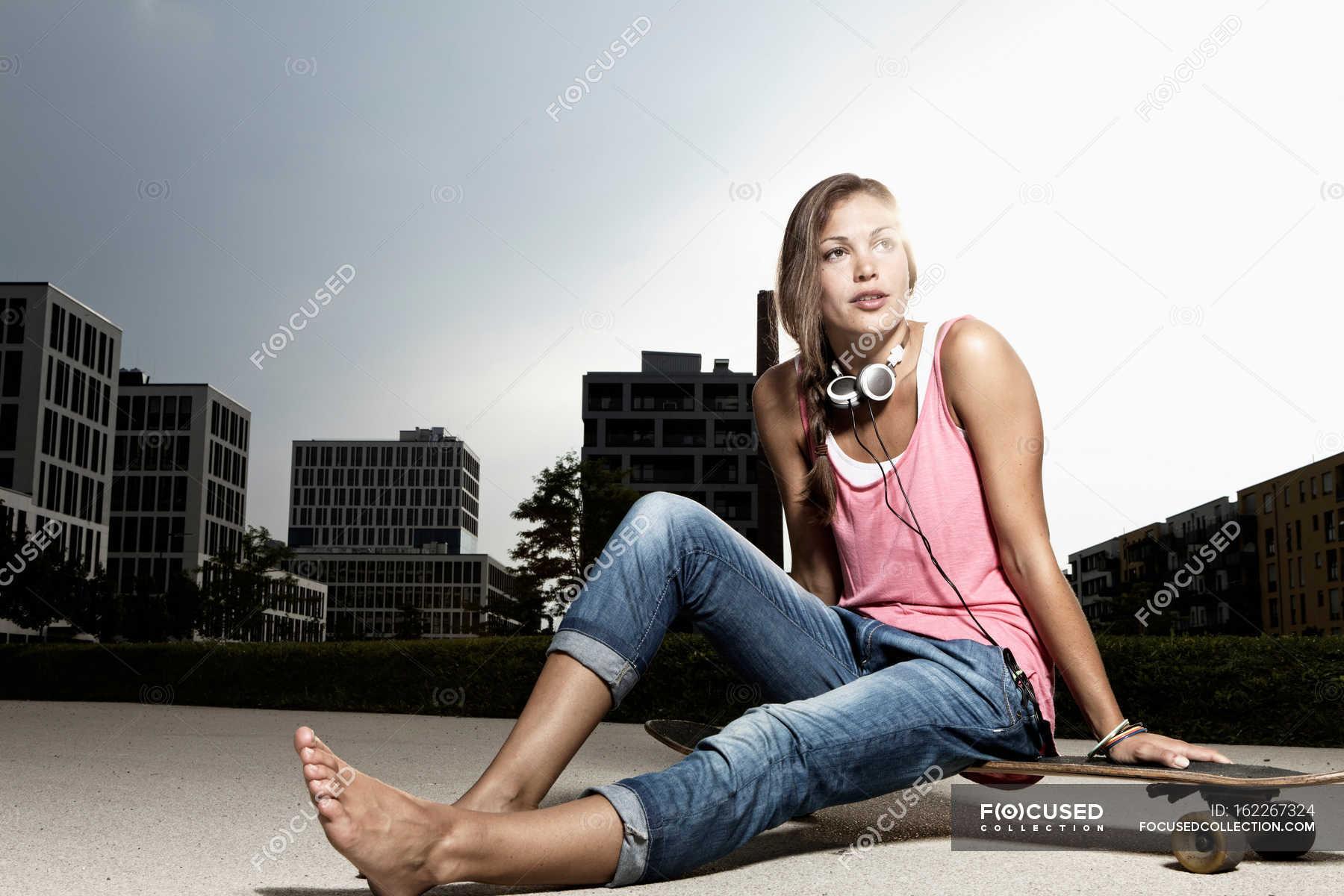 https://st.focusedcollection.com/13397678/i/1800/focused_162267324-stock-photo-woman-sitting-on-skateboard.jpg