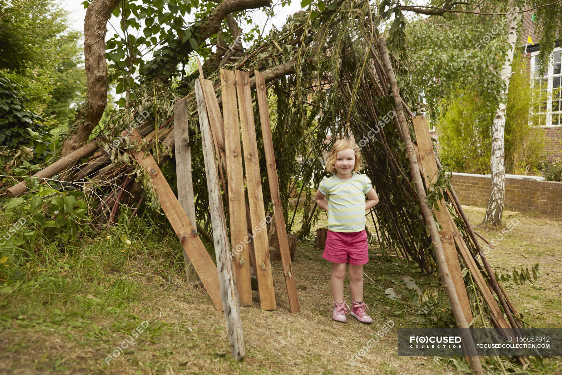 Portrait of girl with hands on hips in garden den — Stock Photo ...