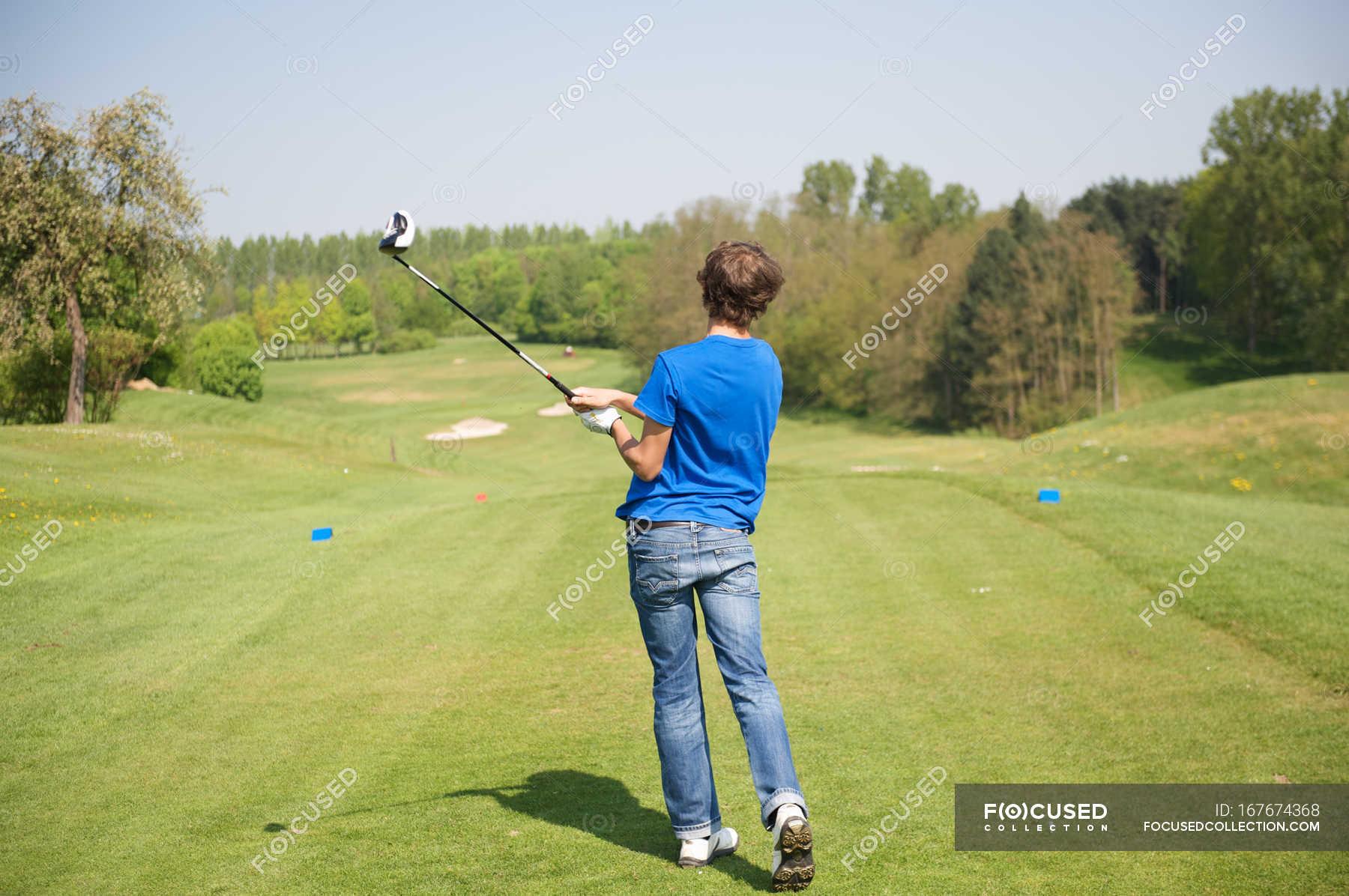 Rear view of boy swinging club on golf course ...