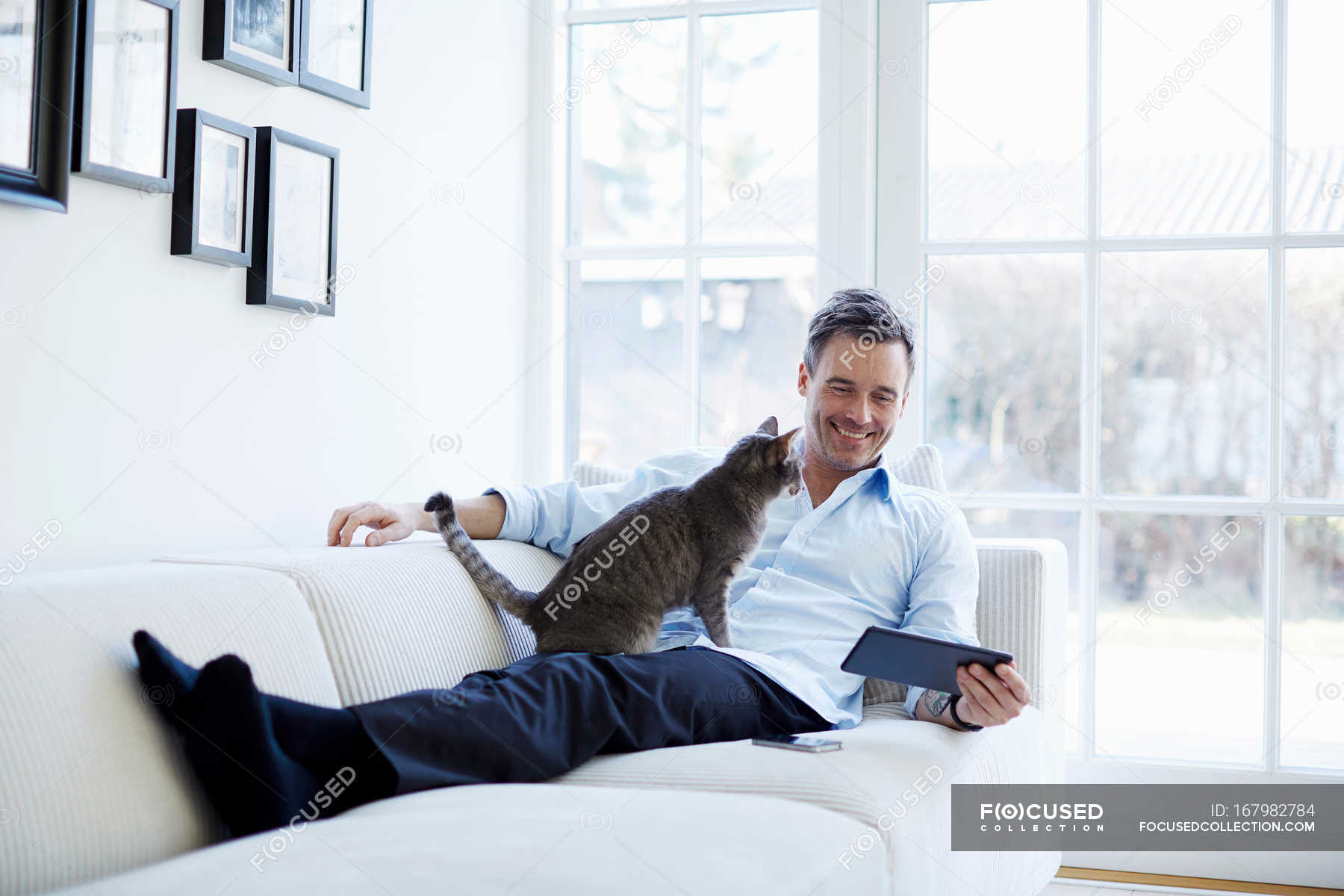 Man Relaxing On Sofa Using Digital