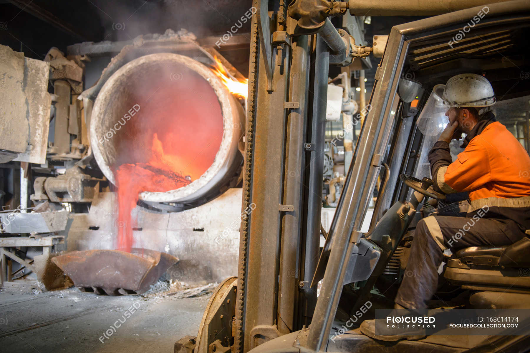 Worker sitting in forklift truck watching furnace in