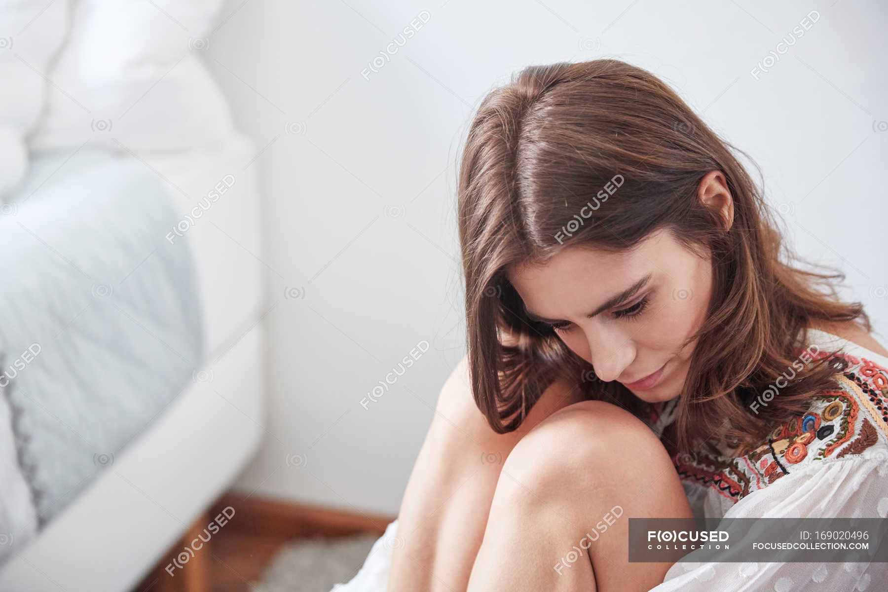 Young Woman Sitting On Floor Near Bed Hugging Knees Brown Hair