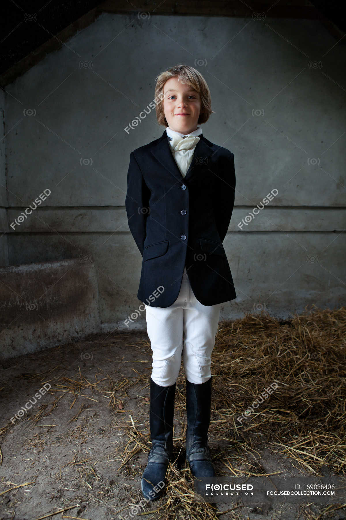 Boy Standing In Horse Riding Clothes In Stable Smiling Child Stock Photo 169036406