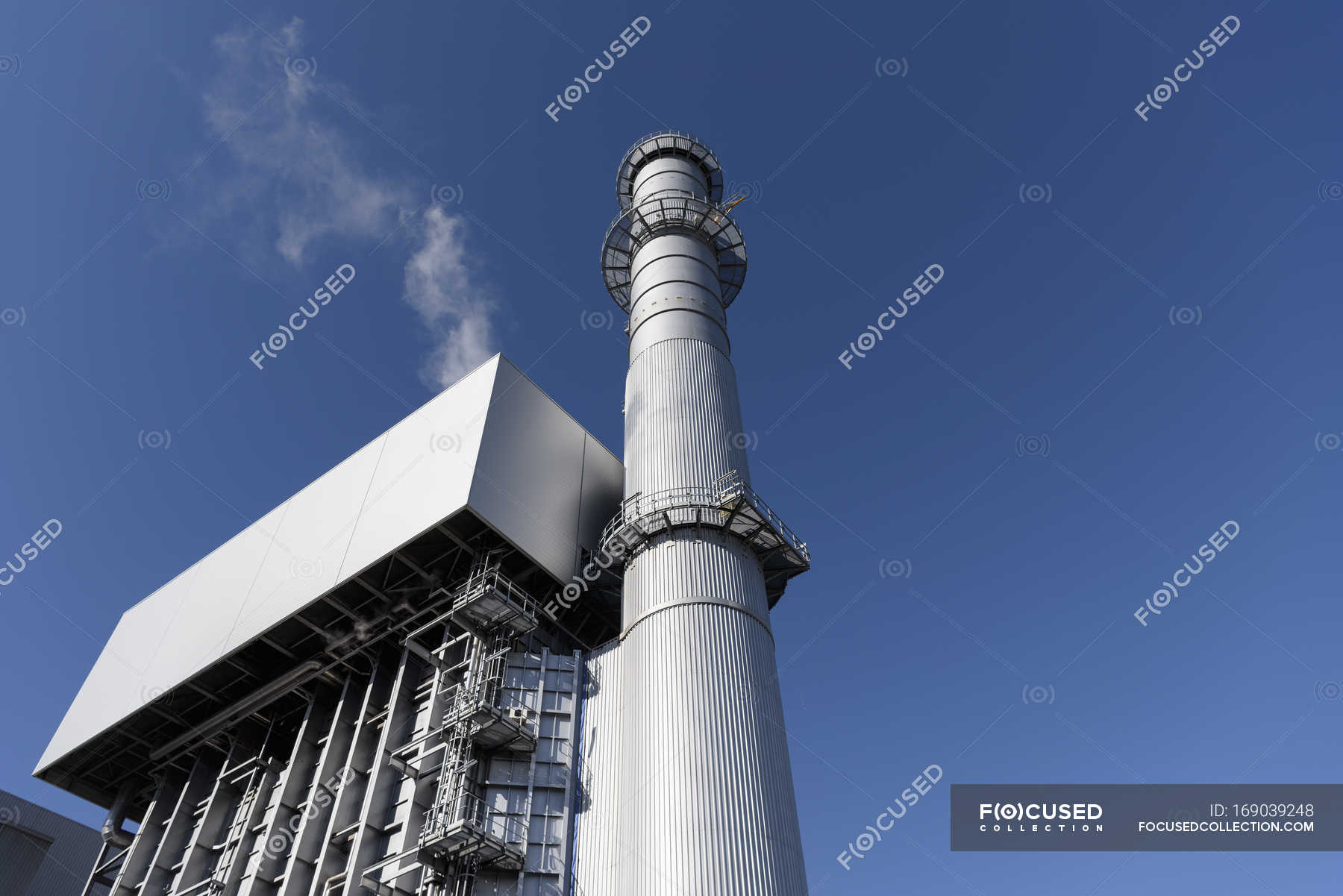 Low angle view of boiler and stack at gas fired power station ...