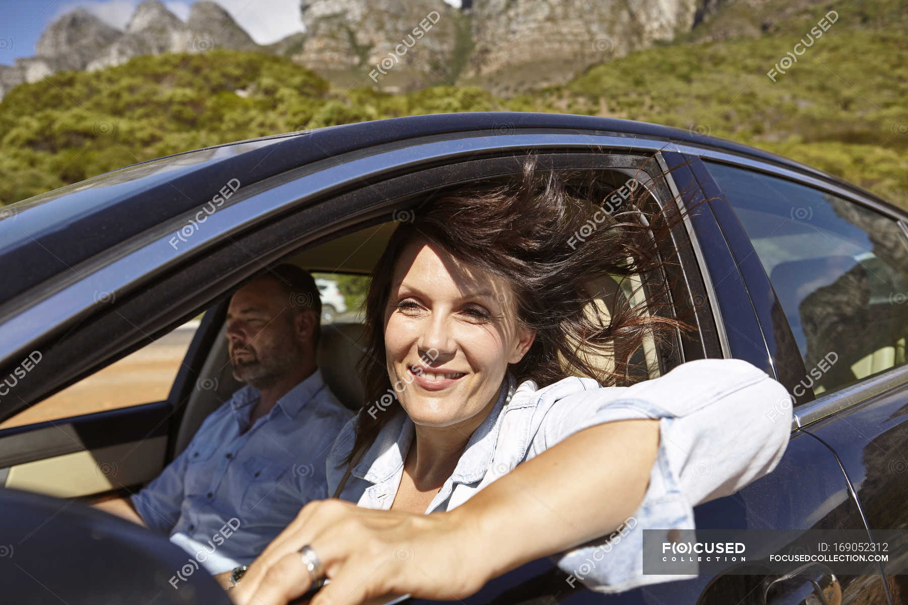 Couple In Car Driving Along Rural Road Woman Leaning On Open Window Cape Town South Africa Stock Photo 169052312