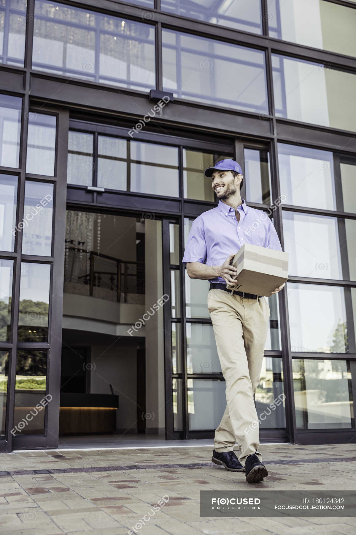 b140234b9 Delivery man carrying package outside office — one person, front ...