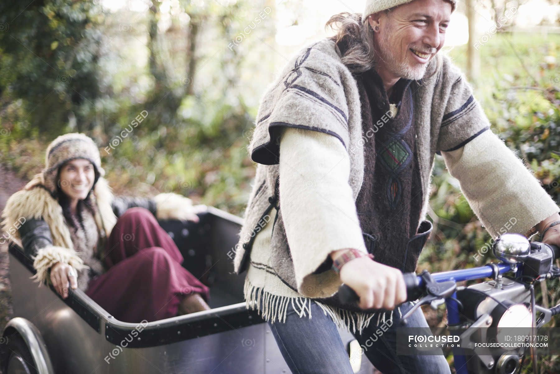 mature hippy couple riding tricycle and trailer on rural road