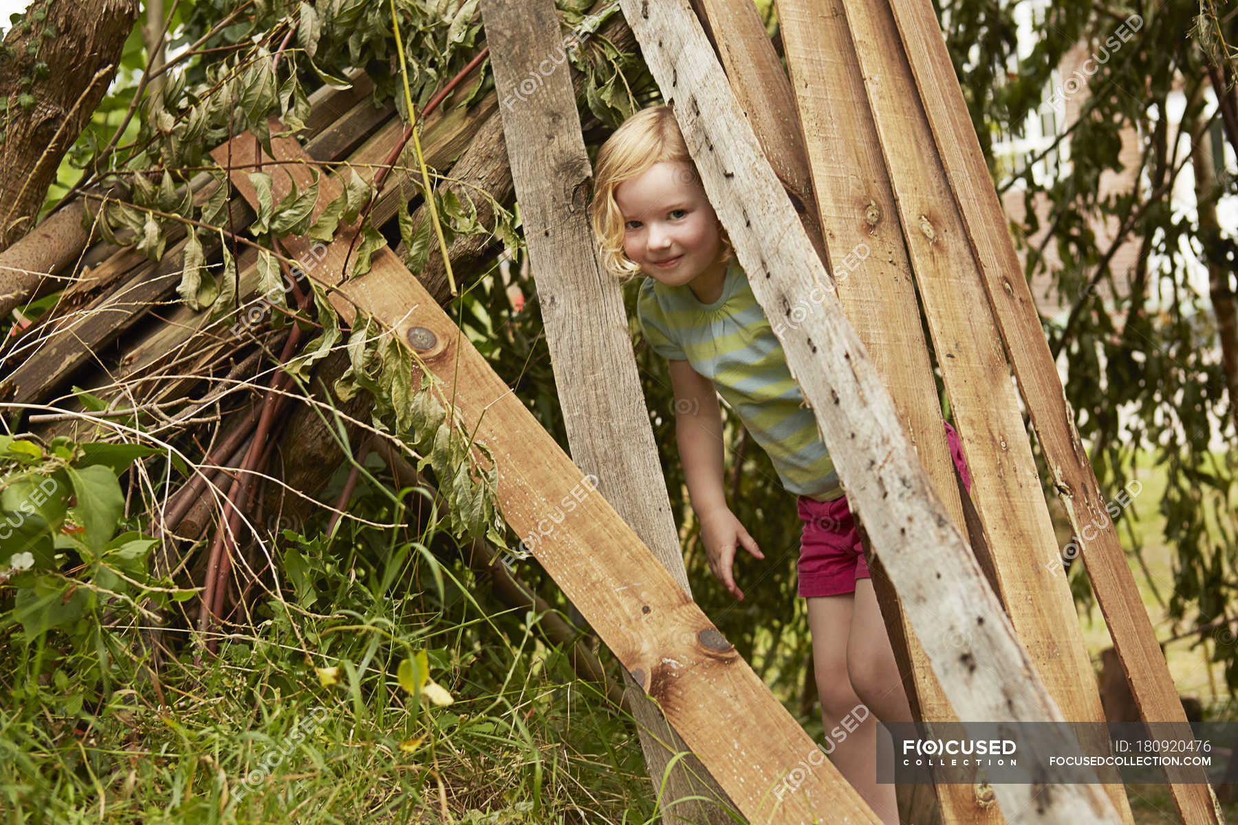Portrait of girl hiding in garden den — Stock Photo | #180920476