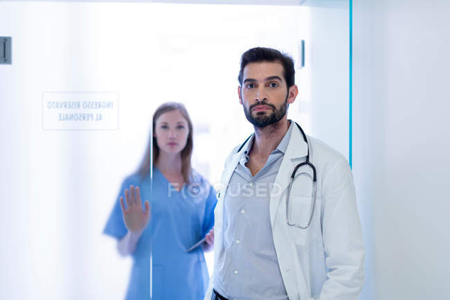 Doctors in hospital looking at camera — Stock Photo