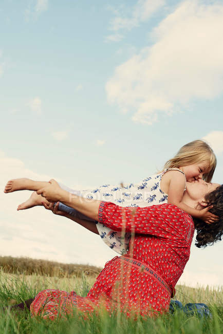 Pregnant woman kissing daughter — Stock Photo