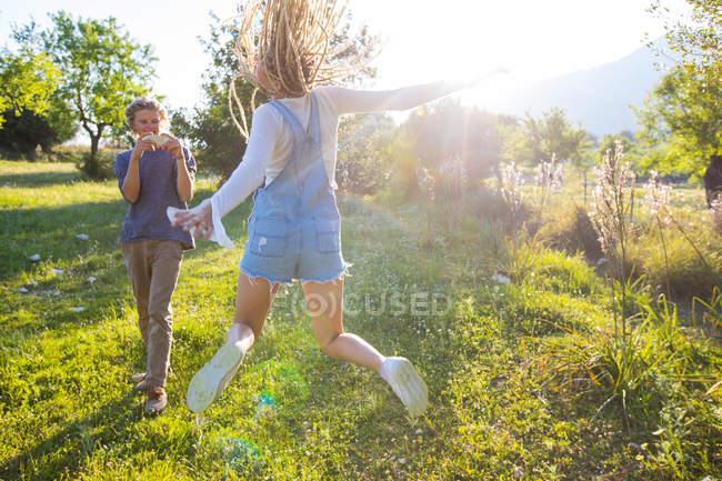 Женщина, прыгающая в поле, сфотографирована парнем — стоковое фото