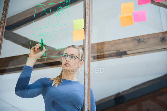 Female designer drawing on window — Stock Photo