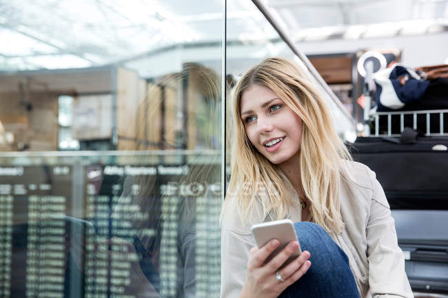 Woman with smartphone gazing in airport terminal — Stock Photo