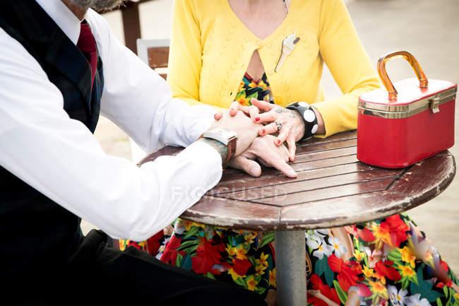Paar hält Händchen am Tisch — Stockfoto