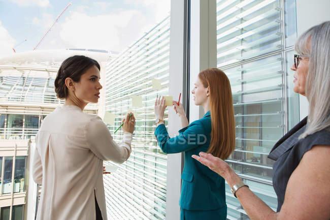 Femmes d'affaires, idées sur la vitre de remue-méninges — Photo de stock