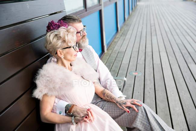 Пара, сидя на скамейке Пирс — стоковое фото