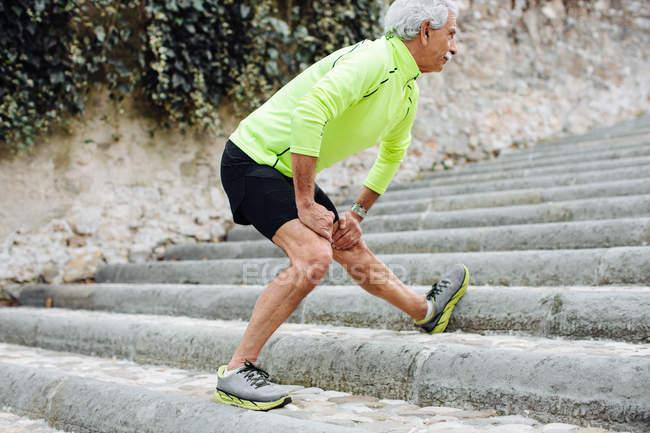 Людина розтягування ногою крок — стокове фото