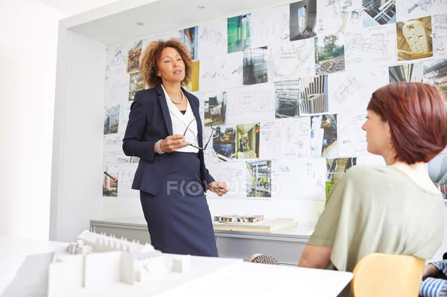 Female architect explaining to colleague — Stock Photo