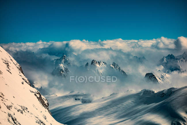 Clouds on snow capped mountain peaks — Stock Photo