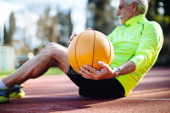 Людина робить sit з баскетболу — стокове фото