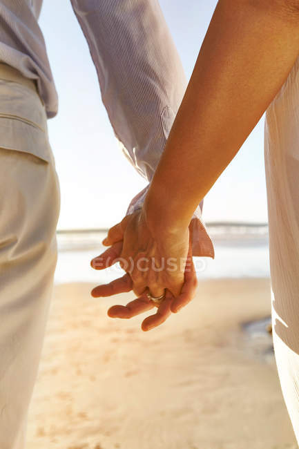 Mature couple holding hands at beach — Stock Photo