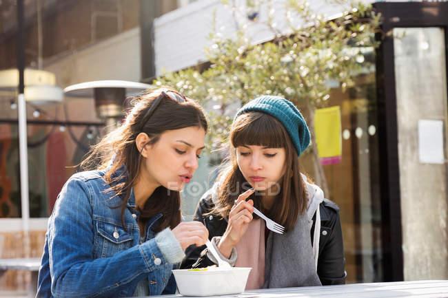 Young women eating takeaway food — Stock Photo