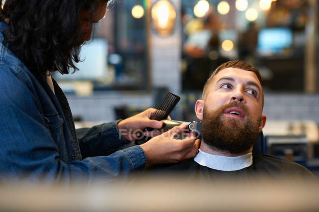 Hairdresser trimming customers beard — Stock Photo