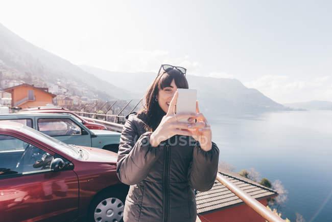 Жінка приймає смартфон selfie на березі озера — стокове фото