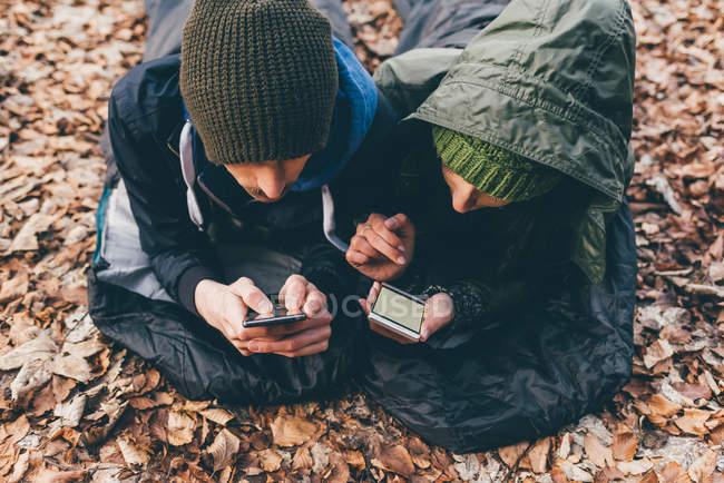 Coppia sdraiata nei sacchi a pelo guardando gli smartphone — Foto stock