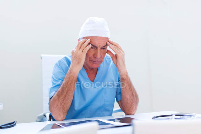 Doctor at desk, head in hands — Stock Photo