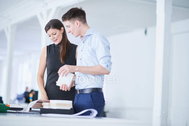 Colleagues in office looking at architectural model — Stock Photo