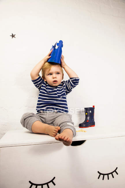 Male toddler sitting on toy chest — Stock Photo