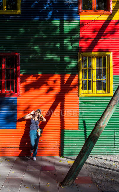 Woman leaning against colorful house — Stock Photo