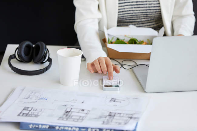 Female designer pressing smartphone — Stock Photo