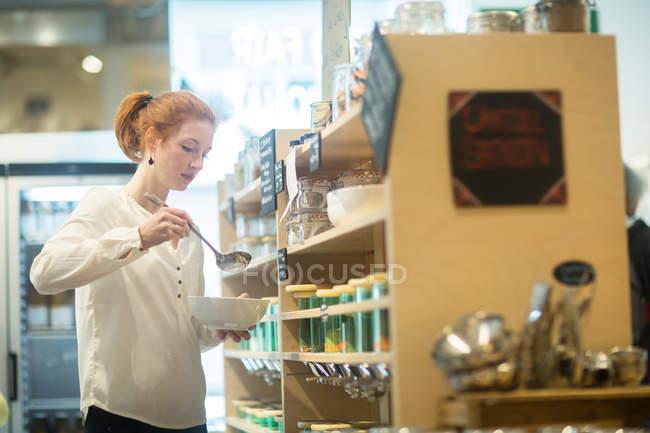 Woman using self service dispensers — Stock Photo
